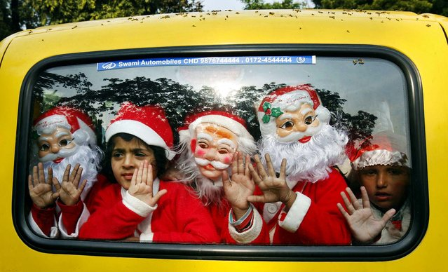 Children dressed in Santa Claus costumes wave after attending Christmas celebrations at a church in the northern Indian city of Chandigarh, on December 23, 2013. (Photo by Ajay Verma/Reuters)