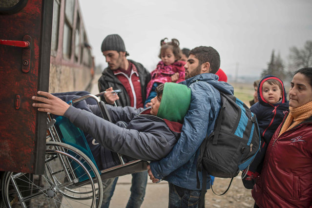 A man helps another young man in a wheelchair as migrants and refugees board a train after crossing the Greek-Macedonian border, near Gevgelija, on February 24, 2016. Balkan countries along the well-trodden migrant path towards northern Europe met on February 24 to explore ways to stem the flow despite growing fears that tighter controls will spark a humanitarian crisis, particularly in Greece. (Photo by Robert Atanasovski/AFP Photo)
