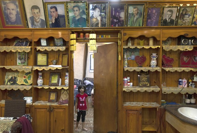 A Palestinian girl stands under framed portraits of family members, some of them were killed by the Israeli army according to Bahjat al-Alami, the grandfather of slain Mohammed al-Alami, 12, at the family house, in the West Bank village of Beit Ummar, near Hebron, Wednesday, August 4, 2021. (Photo by Nasser Nasser/AP Photo)