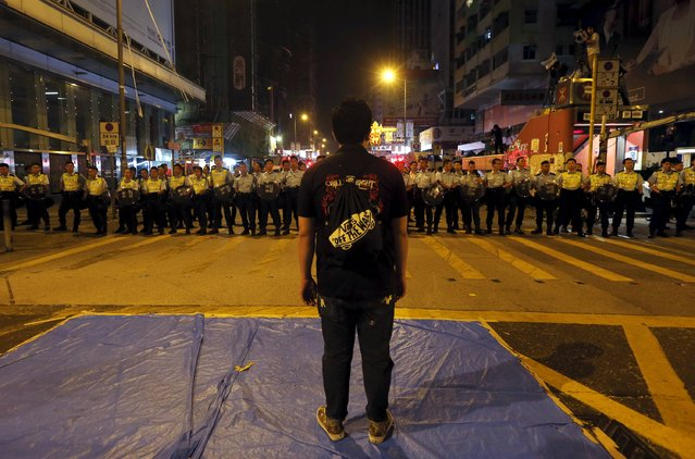 A pro-democracy protester stands in front of a line of riot police at Mongkok shopping district in Hong Kong early, in this October 17, 2014 file photo. (Photo by Bobby Yip/Reuters)