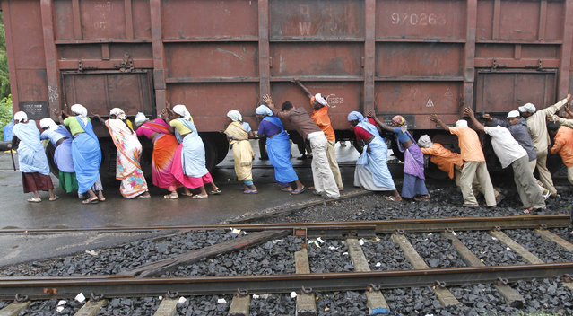 Railway workers push a wagon loaded with coal back to its track after it derailed at Sabarmati power house in the western Indian city of Ahmedabad, September 7, 2011. (Photo by Amit Dave/Reuters)