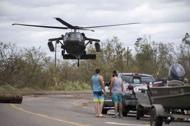 A military helicopter lands on Highway 51 where water is still crossing parts of the road in LaPlace, La., on the morning after Hurricane Ida, Monday, August 30, 2021. (Photo by Chris Granger/The Times-Picayune/The New Orleans Advocate via AP Photo)