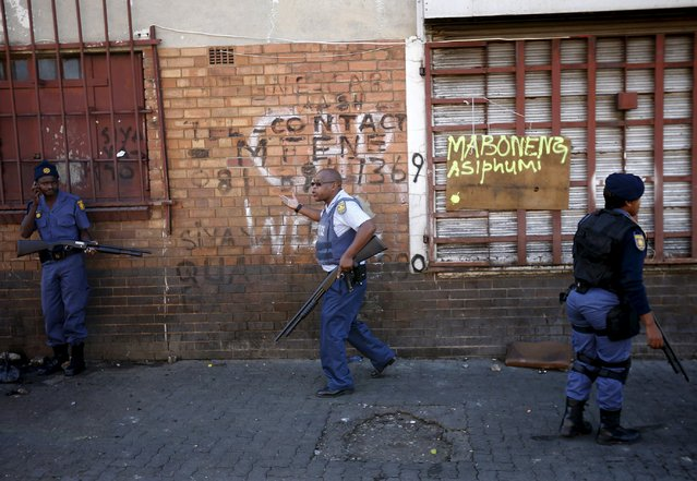 Police officers gesture after firing rubber bullets to disperse African immigrants who were carrying machetes in Johannesburg, April 17, 2015. (Photo by Siphiwe Sibeko/Reuters)