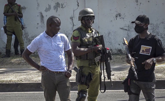 In this image made from video, security forces gather near a body in the street near the French embassy in Dar es Salaam, Tanzania Wednesday, August 25, 2021. (Photo by AP Photo/Stringer)