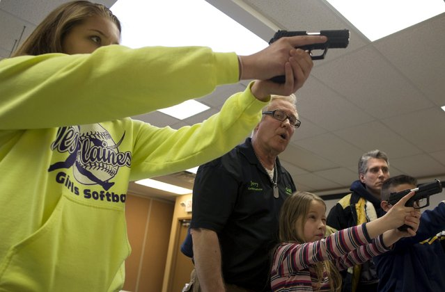 Instructor Jerry Kau (C) shows students Samantha Dolatowski (L) and Joanna Zuber how to hold a handgun during a Youth Handgun Safety Class at GAT Guns in East Dundee, Illinois, April 21, 2015. (Photo by Jim Young/Reuters)