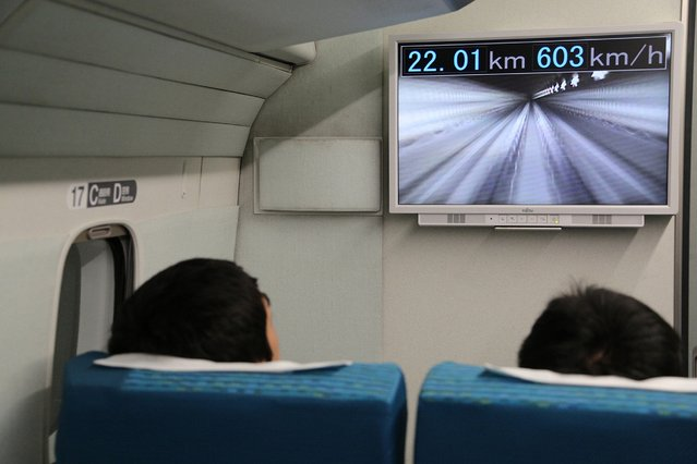 "This Central Japan Railway hand out picture shows passengers watching a monitor in the company's seven-car maglev – short for ""magnetic levitation"" – train while setting a new world speed record in a test run near Mount Fuji, clocking more than 600 kilometres (373 miles) an hour on April 21, 2015. The new record came less than a week after the company clocked 590kph, by breaking its own 2003 record of 581 kph. (Photo by AFP Photo/JIJI Press)"