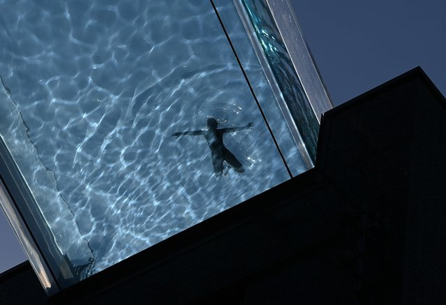 A person relaxes during hot weather at the Embassy Gardens Sky Pool, a transparent acrylic swimming pool suspended between two buildings, in London, Britain, September 7, 2021. (Photo by Toby Melville/Reuters)