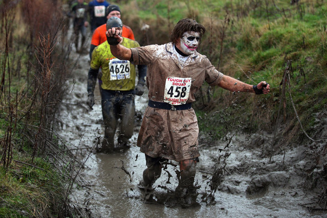 A fancy dress competitor wades through water during the Tough Guy Challenge on January 26, 2014 in Telford, England. (Photo by Bryn Lennon/Getty Images)