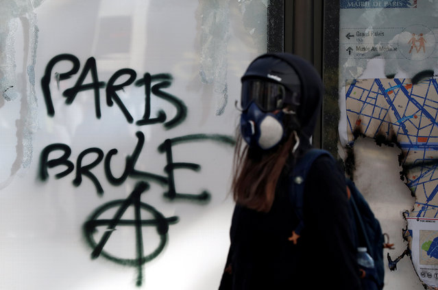 """A protester walks past a graffiti during a demonstration by the """"yellow vests"""" movement in Paris, France, March 16, 2019. The graffiti reads: """"Paris burns"""". Paris police say more than 100 people have been arrested amid rioting in the French capital by yellow vest protesters and clashes with police. They set life-threatening fires, smashed up luxury stores and clashed with police firing tear gas and water cannon. (Photo by Benoit Tessier/Reuters)"""