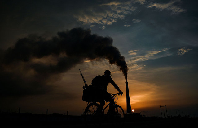 A man ridies his bicycle near the Ernesto Guevara thermoelectric plant in Santa Cruz del Norte, Mayabeque province, Cuba on September 20, 2021. (Photo by Yamil Lage/AFP Photo)