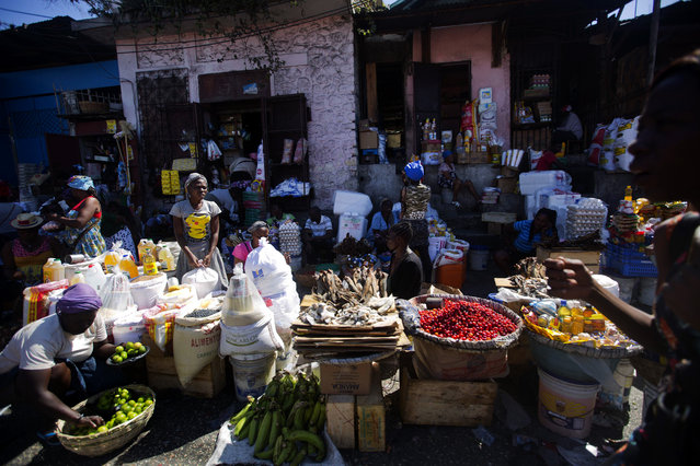 Vendors wait for clients at an open-air market in Port-au-Prince, Haiti, Monday, February 18, 2019. Businesses and government offices slowly reopened across Haiti on Monday after more than a week of violent demonstrations over prices that have doubled for food, gas and other basic goods in recent weeks and allegations of government corruption. (Photo by Dieu Nalio Chery/AP Photo)