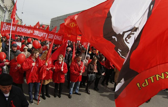 Communists carry a flag depicting Vladimir Lenin, the Soviet Union founder, during a tradition May Day march in St.Petersburg, Russia, Friday, May 1, 2015. (Photo by Dmitry Lovetsky/AP Photo)