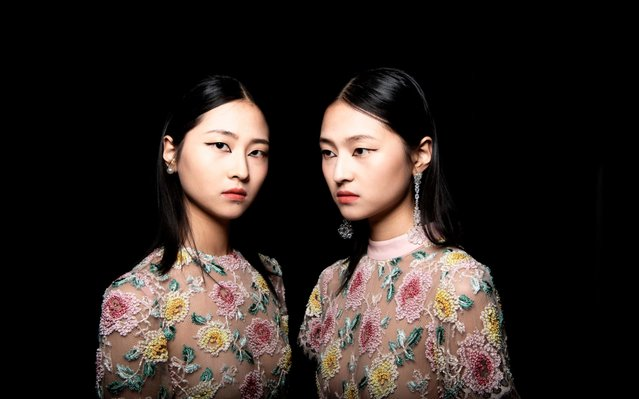 Two models pose backstage before presenting the collection of Chinese designer Zhang Peng during the China Fashion Week in Beijing on March 29, 2019. (Photo by Fred Dufour/AFP Photo)