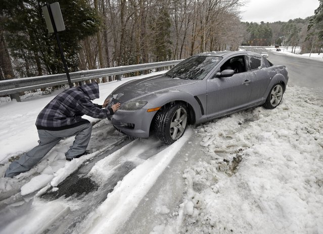 Passerby Leo Cruz helps push a car from the frozen roadside in Chapel Hill, N.C., Thursday, February 13, 2014. The owner abandoned the car overnight during the storm. The National Weather Service issued a winter storm warning lasting into Thursday covering 95 of the state's 100 counties. (Photo by Gerry Broome/AP Photo)