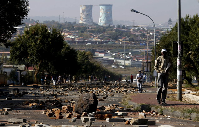 A man walks on a street filled with rocks and stones left behind by protesters who were dispersed by police in Soweto May 7, 2015. South African police fired rubber bullets on Wednesday to disperse angry demonstrators who set tyres alight while protesting against what they called the unaffordable electricity prices of state utility Eskom, a Reuters witness said. (Photo by Siphiwe Sibeko/Reuters)