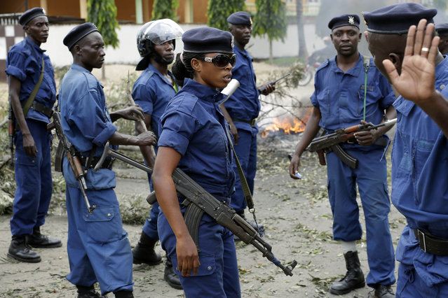 Police clear and secure a barricade in the Kinindo district of Bujumbura, Burundi, Wednesday May 6, 2015. Anti-government demonstrations continue Wednesday and protesters regularly set road blocks in Burundi's capital to protest after the constitutional court validated  President Pierre Nkurunziza's decision to seek a third term in office. (Photo by Jerome Delay/AP Photo)