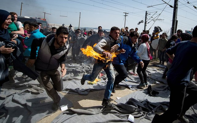 A man runs after he tried to put himself on fire during a protest at a makeshift camp at the Greek-Macedonian border near the village of Idomeni on March 22, 2016. Greece will not be able to start sending refugees back to Turkey from March 20, 2016, the government said, as the country struggles to implement a key deal aimed at easing Europe's migrant crisis. The numbers are daunting: officials said as of Saturday there were 47,500 migrants in Greece, including 8,200 on the islands and 10,500 massed at the Idomeni camp on the Macedonian border. (Photo by Andrej Isakovic/AFP Photo)