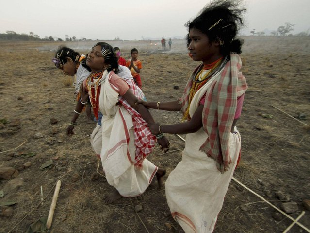 During the dancing in trance at the Niyamraja Festival many female participants faint due to exhaustion. (Photo by Biswaranjan Rout/AP Photo)