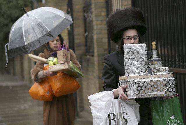 Members of the Jewish community carry gifts as they celebrate the festival of Purim in Stamford Hill in north London, Britain March 24, 2016. (Photo by Neil Hall/Reuters)