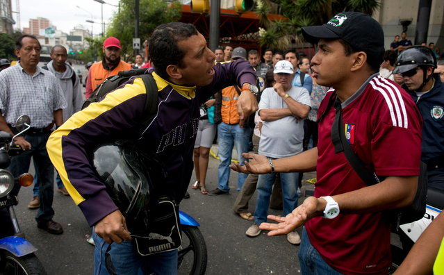 A motor cycle driver, left, argues with demonstrator blocking the highway at Altamira neighborhood in Caracas, Venezuela, Monday, February 24, 2014. Traffic has come to a halt in parts of the Venezuelan capital because of barricades set up by opposition protesters across major thoroughfares. (Photo by Rodrigo Abd/AP Photo)
