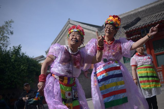 Two elderly women perform a dance at a park near the Forbidden City in Beijing on May 3, 2015. (Photo by Wang Zhao/AFP Photo)