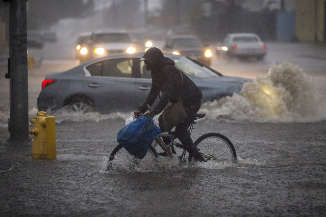 A bicyclist rides along a flooded street as a powerful storm moves across Southern California on February 17, 2017 in Sun Valley, California. After years of severe drought, heavy winter rains have come to the state, and with them, the issuance of flash flood watches in Santa Barbara, Ventura and Los Angeles counties, and the evacuation of hundreds of residents from Duarte, California for fear of flash flooding from areas denuded by a wildfire last year. (Photo by David McNew/Getty Images)