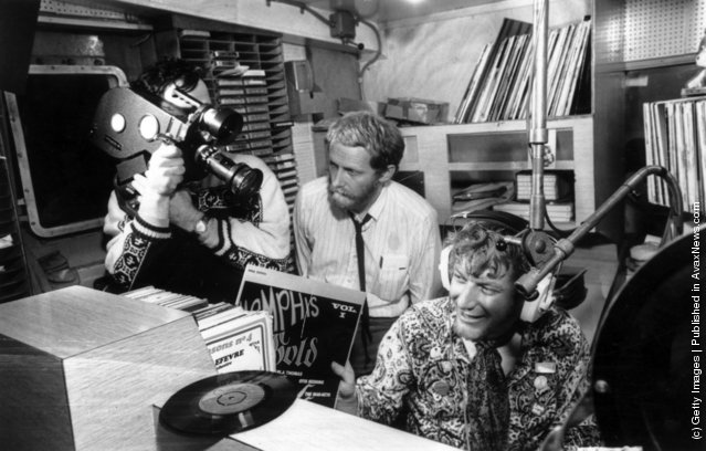 The World in Action team making a program about the pirate radio ship Caroline, filmed by Paddy Searle, and produced by Mike Hodges. The DJ being filmed is Robbie Dale, and Hodges is standing behind him