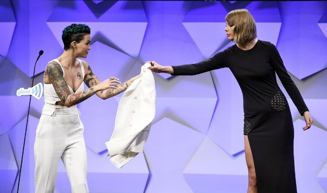 Actress Ruby Rose, left, recipient of the Stephen F. Kolzak Award, hands her jacket to presenter Taylor Swift during the 27th Annual GLAAD Media Awards at the Beverly Hilton on Saturday, April 2, 2016, in Beverly Hills, Calif. (Photo by Chris Pizzello/Invision/AP Photo)