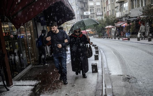 People walk under a shelter during a sudden hail-storm on April 22, 2015, in Istanbul. (Photo by Bulent Kilic/AFP Photo)