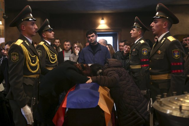 People surround a coffin with the body of an Armenian serviceman, who was killed in clashes over the breakaway Nagorno-Karabakh region according to Armenian media, during a memorial service at a church in Yerevan, Armenia, April 5, 2016. (Photo by Hrant Khachatryan/Reuters/PAN Photo)