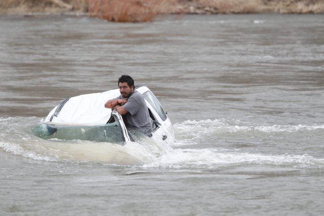 A man stranded in his car in the Yakima River in Wapato, Wash., on Sunday, March 16, 2014 in Wapato, Wash.  Yakima County emergency responders rescued the man Sunday evening.  A witness saw one man make it to shore, but another man was apparently trapped in the car as it filled with frigid water. The sheriff's swiftwater rescue boat arrived in time to pull him to safety. He was taken to a hospital to be treated for hypothermia and possible injuries from the accident. (Photo by Kaitlyn Bernauer/AP Photo/Yakima Herald-Republic)