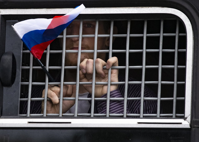 A detained protester holds a Russian flag while looking out of a police bus window during a march in Moscow, Russia, Wednesday, June 12, 2019. (Photo by Alexander Zemlianichenko/AP Photo)