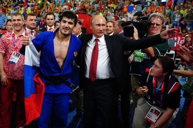 Russian President Vladimir Putin (C) celebrates Tagir Khaibulaev of Russia's gold medal in the Men's -100 kg Judo on Day 6 of the London 2012 Olympic Games at ExCeL on August 2, 2012 in London, England. (Photo by Laurence Griffiths/Getty Images)