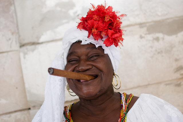 An old woman smokes a cigar at Old Havana's Plaza de la Catedral on February 07, 2006 in Havana, Cuba. (Photo by Marco Prosch/Getty Images)