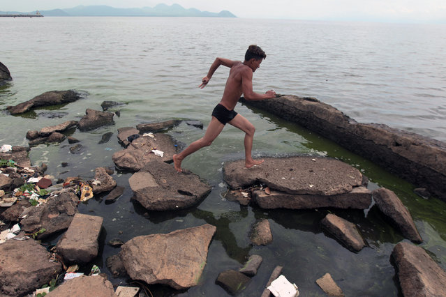 A boy runs as he prepares to jump into the polluted waters of Lake Xolotlan in Managua, Nicaragua on June 5, 2013. The World Environment Day is celebrated annually on June 5 to raise awareness about environmental issues and stimulate political action, according to the United Nations Environment Programme. (Photo by Oswaldo Rivas/Reuters)
