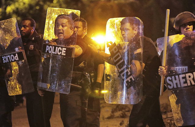 Memphis police brace against the crowd as protesters take to the streets of the Frayser community in anger against the shooting a youth by U.S. Marshals earlier in the evening, Wednesday, June 12, 2019, in Memphis, Tenn. (Photo by Jim Weber/Daily Memphian via AP Photo)