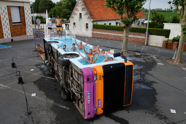 """People bathe in a decommissioned city bus named """"Le bus piscine"""", an artwork by the French artist Benedetto Bufalino in Gosnay near Bethune, France, July 10, 2019. (Photo by Pascal Rossignol/Reuters)"""