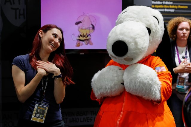 Attendee Georgia Khalil meets the character Snoopy at the pop culture festival Comic Con International during opening night in San Diego, California,U.S., July 17, 2019. (Photo by Mike Blake/Reuters)