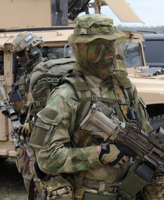 Polish Army special forces soldiers stand with their gear after the NATO Noble Jump exercise on a training range near Swietoszow Zagan, Poland, Thursday, June 18, 2015. (AP Photo/Alik Keplicz)