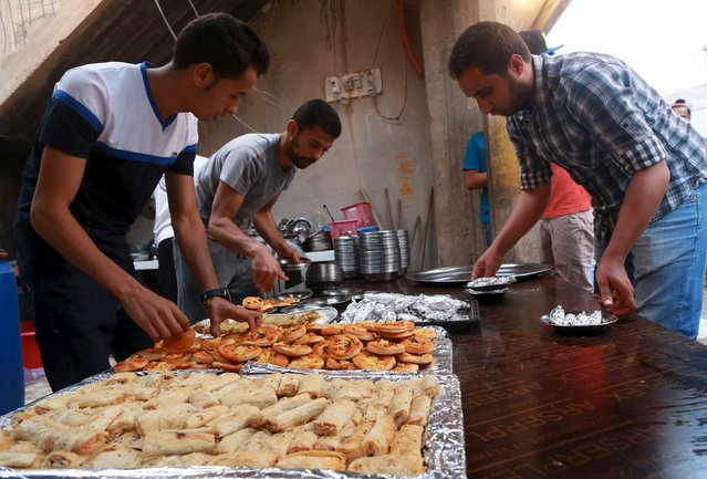 Volunteers prepare food as people wait to eat their Iftar (breaking of fast) meal at tables set up by a charity during the holy fasting month of Ramadan in Benghazi, Libya June 27, 2015. (Photo by Esam Omran Al-Fetori/Reuters)