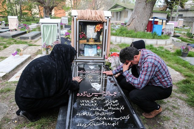 Samereh Alinejad (L) and Abdolghani Hosseinzadeh (R) mourn at the grave of their son Abdolah Hosseinzadeh who was killed by a fellow Iranian, Balal, in a street fight with a knife in 2007, after they spared the life of their son's convicted murderer during his execution ceremony in the northern city of Nowshahr on April 15, 2014. Alinejad spared the life of Balal with an emotional slap in the face as he awaited execution with the noose around his neck, a newspaper resported. (Photo by Araash Khamooshi/AFP Photo/ISNA)