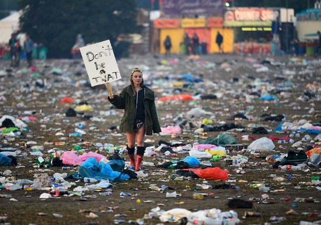 A reveller walks through rubbish left in front of the Pyramid Stage as they leave Worthy Farm in Somerset after the Glastonbury Festival in Britain, June 29, 2015. (Photo by Dylan Martinez/Reuters)