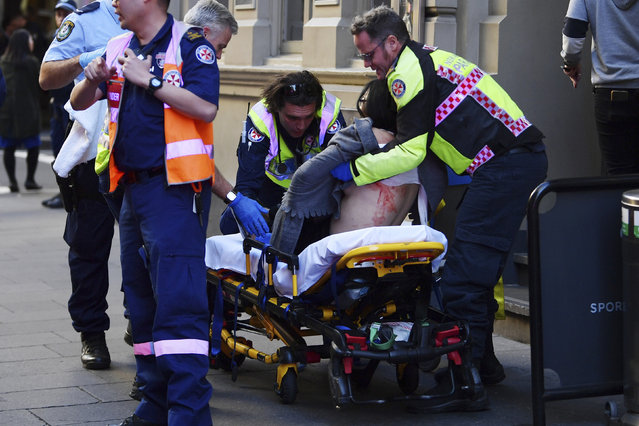 An injured woman is taken by ambulance from Hotel CBD at the corner of King and York Street in Sydney, Australia Tuesday, August 13, 2019. Police and witnesses say a young man yelling about religion and armed with a knife has attempted to stab several people in downtown Sydney before being arrested, with one woman taken to a hospital. (Photo by Dean Lewins/AAP Image via AP Photo)