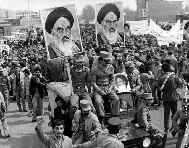 The Iranian Islamic Republic Army demonstrates in solidarity with people in the street during the Iranian revolution. They are carrying posters of the Ayatollah Khomeini, the Iranian religious and political leader, 1979