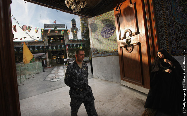An Iraqi Police officer and woman walk at the entrance to the Seid Idrees mosque during preparation for the festival Ashura in Baghdad, Iraq