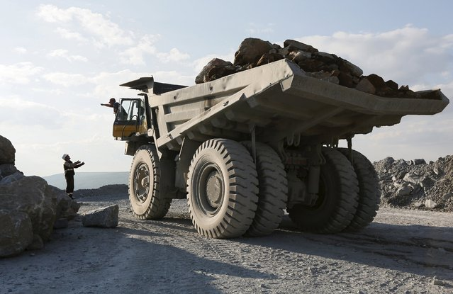 An engineer (L) talks to a driver of a dump truck loaded with gold-bearing soil at the Vostochny opencast of the Olimpiada gold operation, owned by Polyus Gold International company, in Krasnoyarsk region, Eastern Siberia, Russia, June 30, 2015. (Photo by Ilya Naymushin/Reuters)
