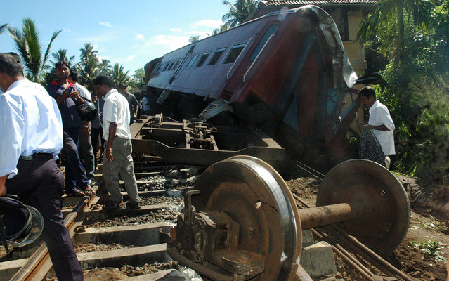 Sri Lankan residents look at derailed carriges after two trains collided in Pothuhera, about 90 kilometers (56 miles) northeast of Colombo on April 30, 2014. At least 68 passengers were injured in the train accident at Pothuhera, police said. (Photo by AFP Photo)