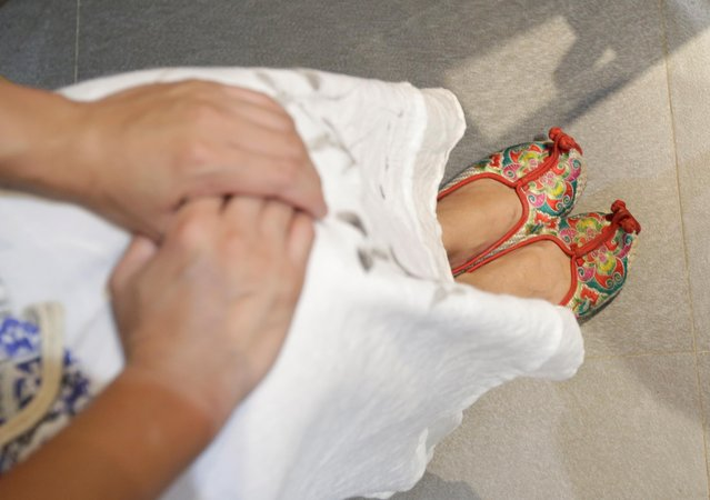 """A woman's traditional shoes are seen as she attends a performance of the """"guqin"""" traditional musical instrument, an ancient seven-stringed zither, at an art space in Beijing, China, August 18, 2019. (Photo by Jason Lee/Reuters)"""