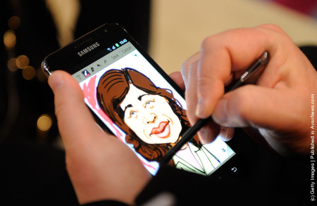 An artist draws caricatures of attendees using the Galaxy Note smartphone with integrated S Pen at the Samsung booth at the 2012 International Consumer Electronics Show