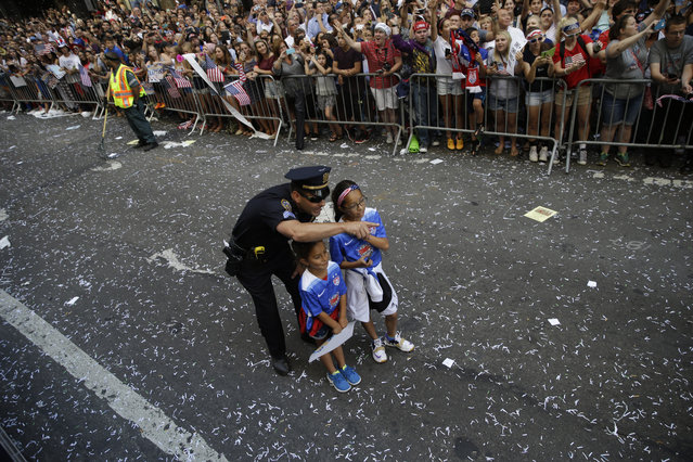 A police officer with two U.S. women's soccer team fans points as the floats with players makes its way up Broadway's Canyon of Heroes during the ticker tape parade to celebrate the World Cup victory, Friday, July 10, 2015, in New York. (Photo by Mary Altaffer/AP Photo)